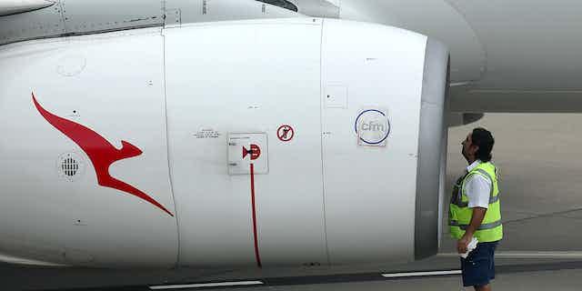 Qantas employee inspects jet engine