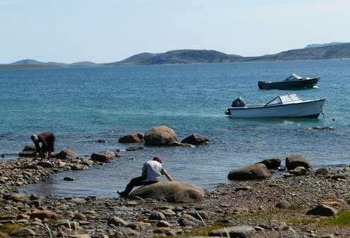 A rocky shore with two people in the foreground and two boats in the water in the background