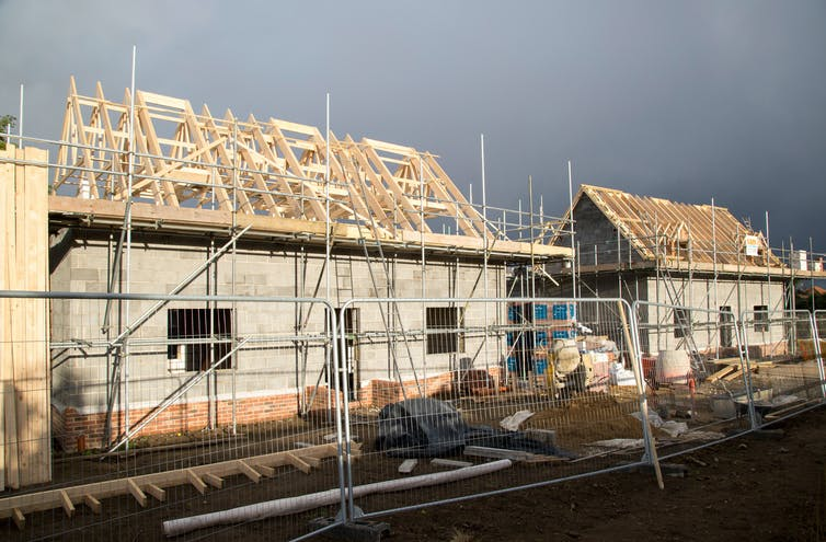 Storm clouds brew over village houses under construction