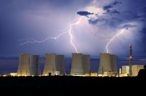 Cooling towers of a nuclear power plant with lightning in the background.