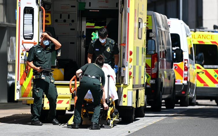 Paramedics transferring a patient from an ambulance into hospital