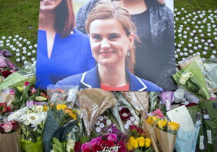 A photograph of murdered MP for Batley and SPen, Jo Cox, above bouquets of flowers.