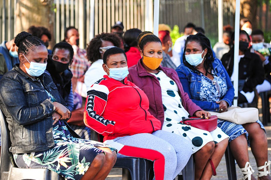 Women wearing face masks sit on chairs in rows