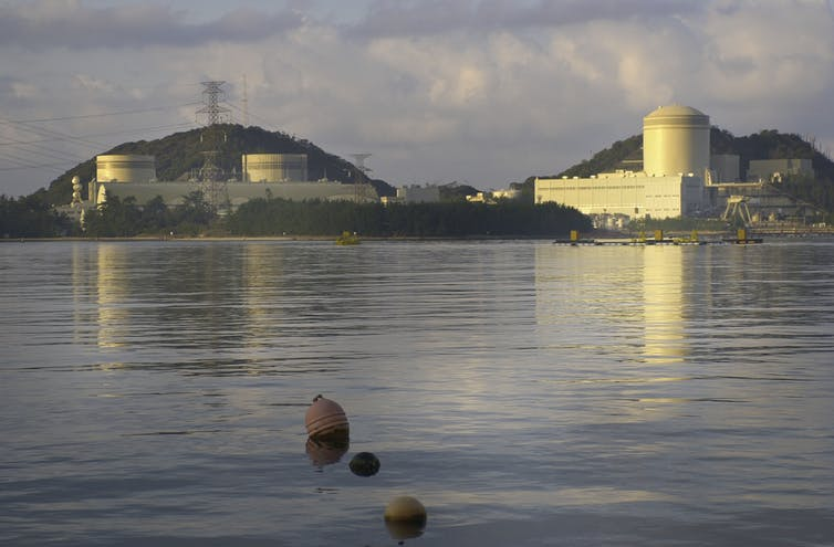 A large nuclear facility on a hill opposite a body of water.