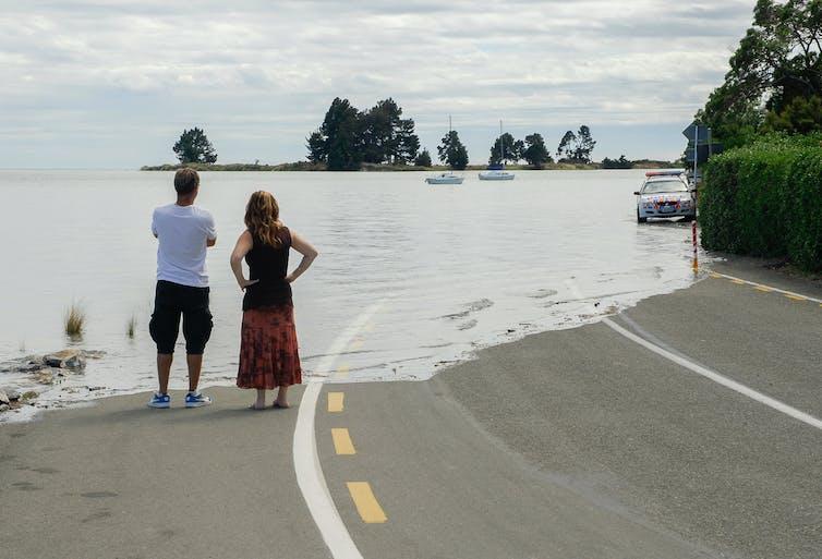 Two people look on as a motorway is engulfed by ocean water.