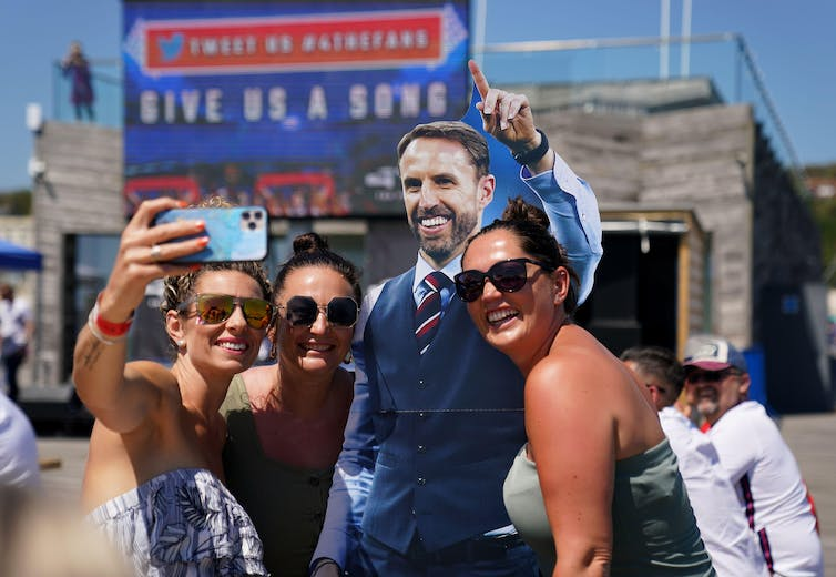 Football fans pose with a cardboard cut out of Gareth Southgate.