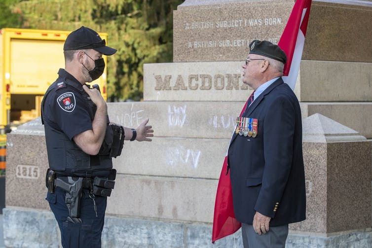 A police officer gestures with to a statue while talking with a veteran holding a Canadian flag.