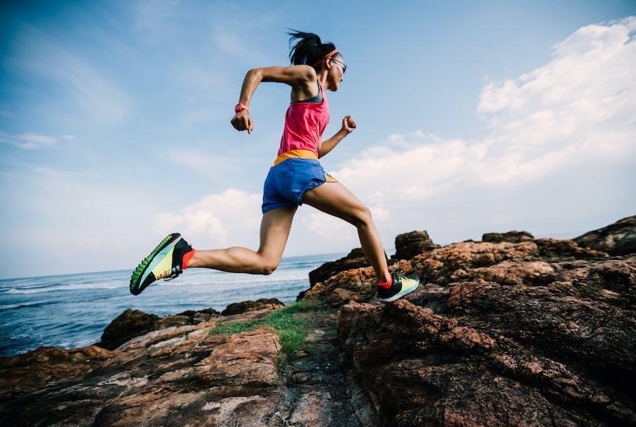 Female trail runner runs up a rocky hill.