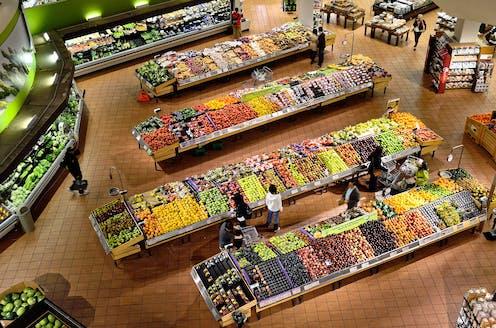 Des gens se promènent dans les allées de fruits et de légumes d'un supermarché.