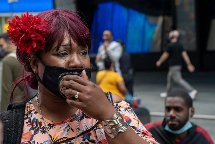 Black woman in a face masks cries on a city street, with a hand over her mouth