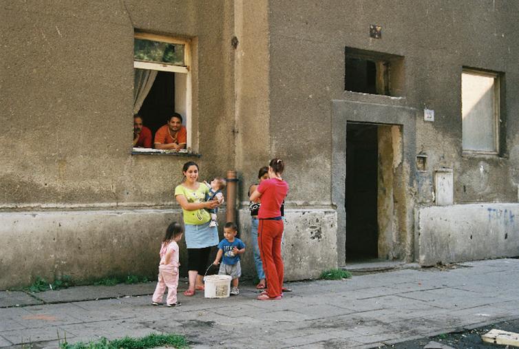 A Roma family outside a slum building.