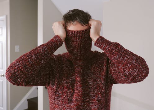 man with turtleneck of sweater pulled over his face