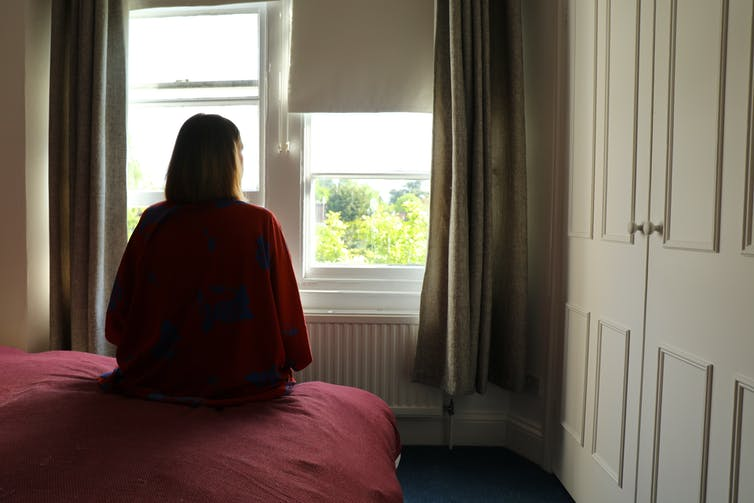 view from behind of woman sitting on bed and looking out window