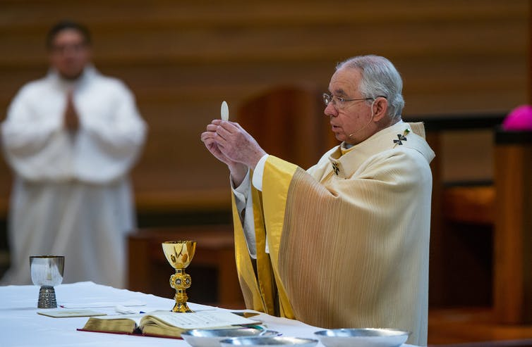 Archbishop Jose H. Gomez holds a Communion wafer during Mass  at the Cathedral of Our Lady of the Angels in downtown Los Angeles in 2020.