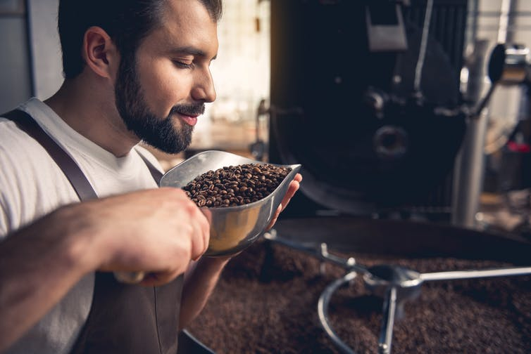 Man smelling coffee beans.
