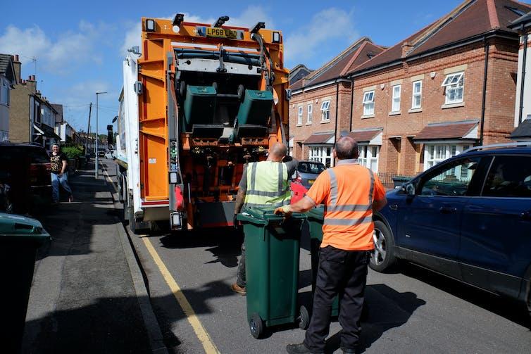 Two men load bins onto a lorry