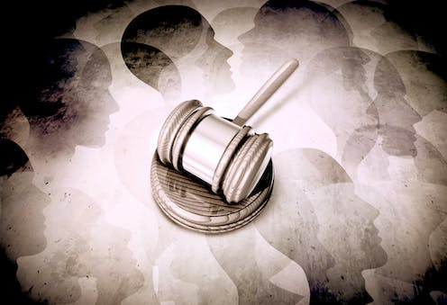 Sepia-toned gavel against a background of abstract human faces