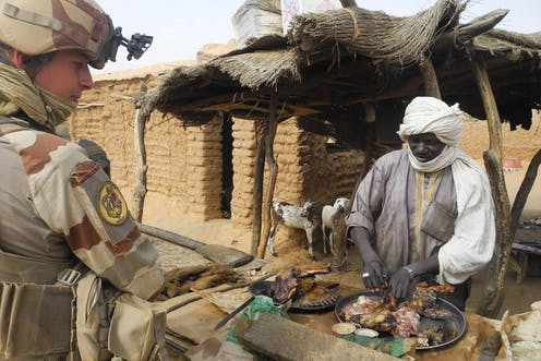 A soldier in full combat gear stands in front of a man arranging meat on a table