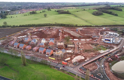 Photo An overhead view of a new development surrounded by green fields