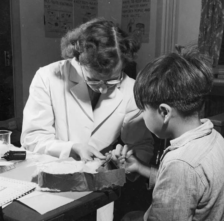 Photo noir et blanc: une infirmière prélève un échantillon de sang sur un petit garçon