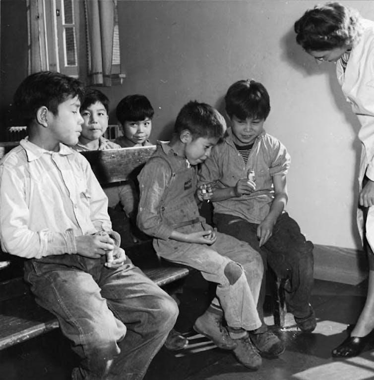 Une infirmière regarde des garçons cracher dans des éprouvettes