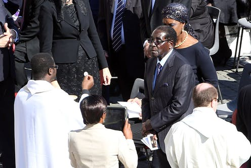 Zimbabwe's ruler Robert Mugabe flanked by his wife Grace receives the communion during the holy mass  held by Pope Francis at St. Peter's Square on October 19, 2014 in Vatican City, Vatican