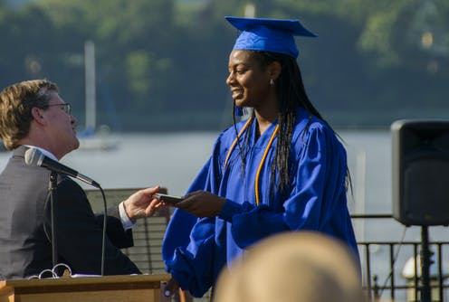 A Black female high schooler receives her diploma.
