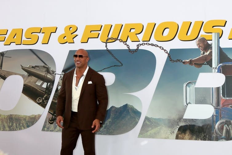 Dwayne Johson standing inn front of a promotional poster for Fast & Furious