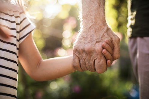 An old man, holding the hand of a young girl