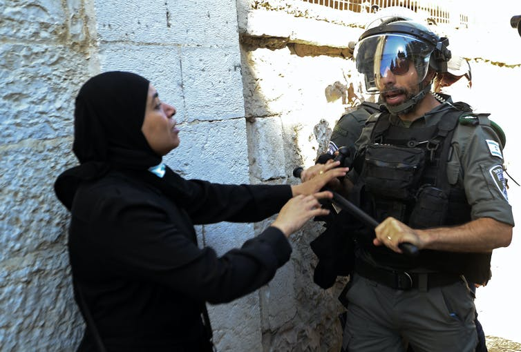 A woman raises her hands as a heavily armoured police officer confronts her.