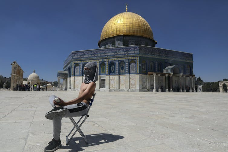 A man in a chair holding a rock sits in the foreground with the Dome of the Rock Mosque in the background.