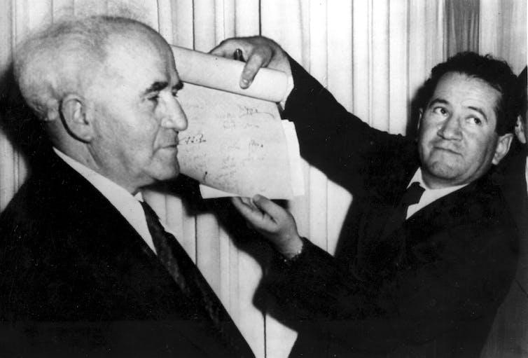 A man unrolls a scroll as David Ben-Gurion looks on.
