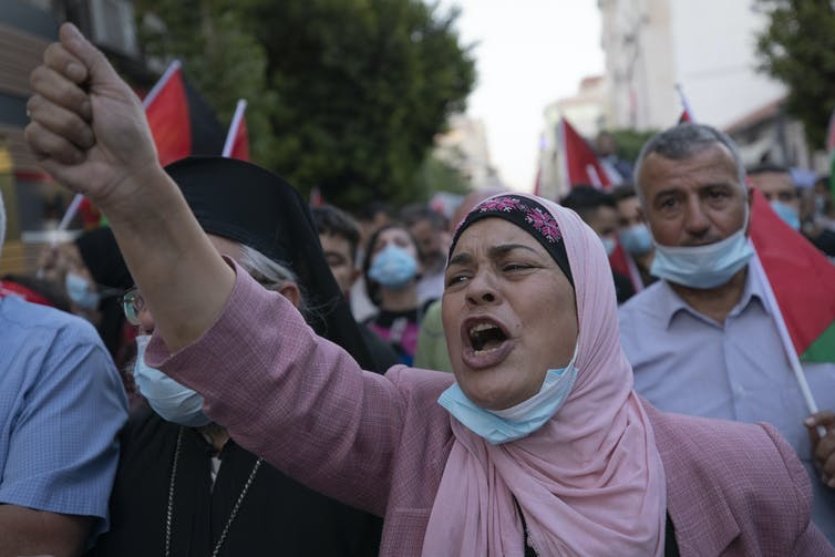 A woman raises her fist in protest.