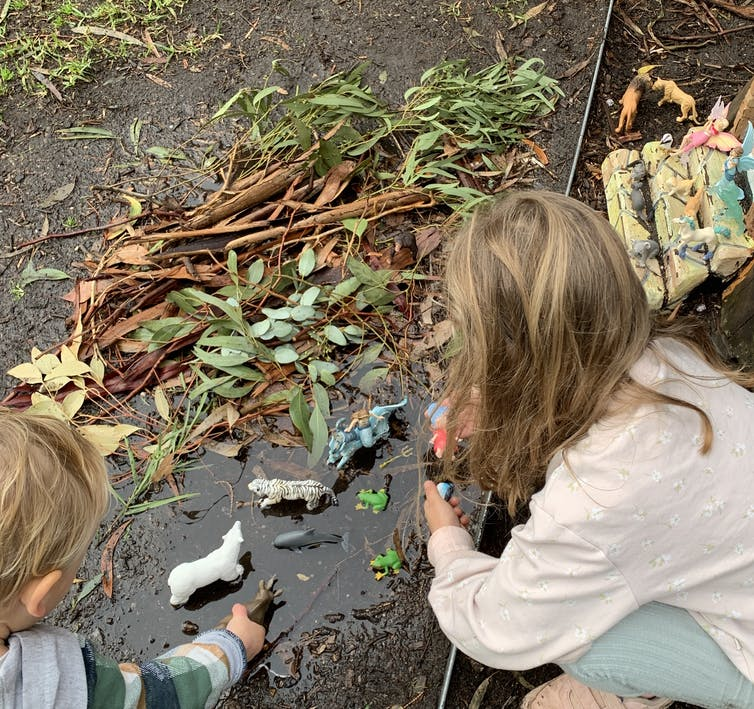 Kids playing with little figurines in the mud.