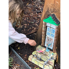 Girl playing with a fairy door in a tree.
