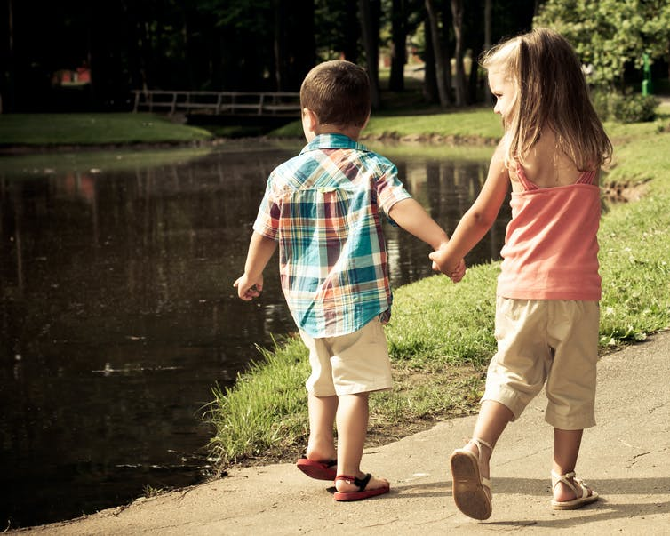 Brother and sister holding hands walking past a lake.