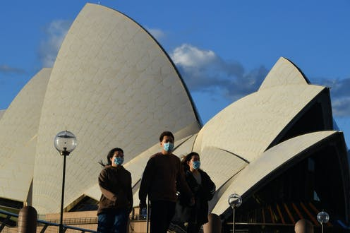 People wearing masks in front of the Sydney Opera House