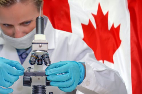 A woman scientist uses a microscope as the Canadian flag waves in the background