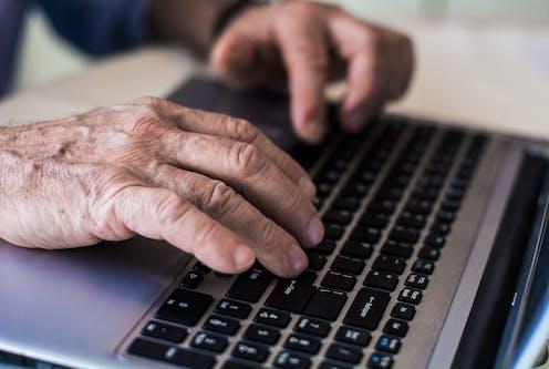 Wrinkled hands on a laptop keyboard.