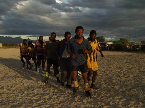 A pack of young men in football clothes form a triangle as they jog towards camera, late afternoon skies.