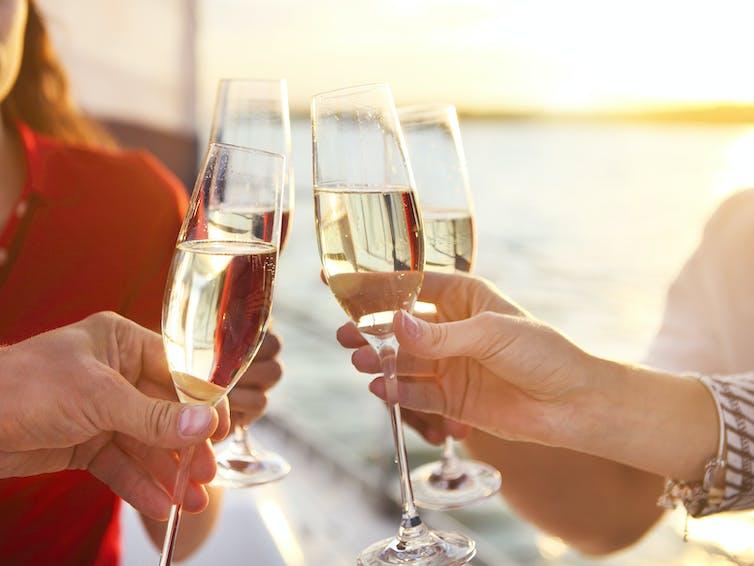 Cuatro personas chocando copas de champán frente a una puesta de sol