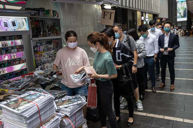 Hongkongers queue at a newstand to buy the final edition of the Apple Daily tabloid newspaper.