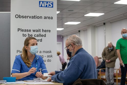A nurse speaking to a man at an NHS vaccination centre