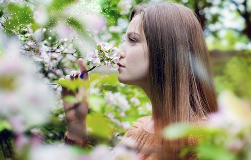 Mujer de perfil oliendo flores de manzano.