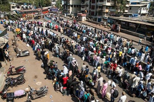 Trabajadores migrantes hacen cola para subir a un autobús que les llevará a la estación de ferrocarril para coger un tren de vuelta a casa durante el confinamiento