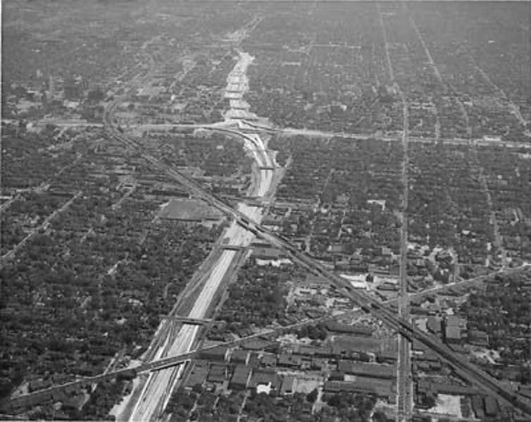 A historic view of Detroit, Michigan, showing the city bisected by an interstate highway.