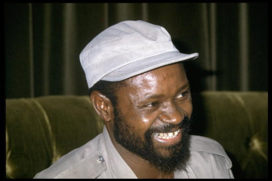 A bearded man wearing a military cap and shirt smiles heartily.