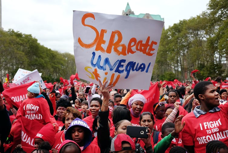 A rally of students and families wearing red T-shirts that say 'I fight to end equality'