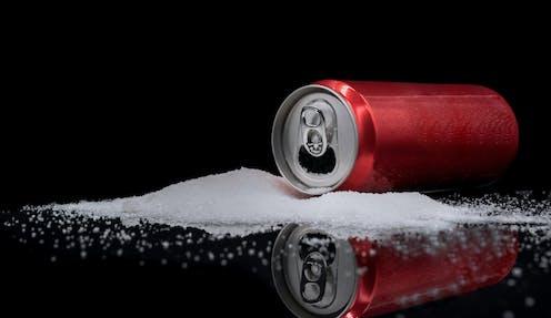 Lata de refresco sobre montón de azúcar.