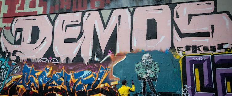 A man stands infront of a mural depicting Bernie Sanders. The word demos is written above.